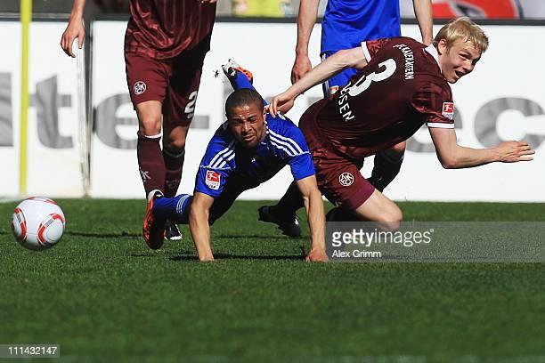 Sidney Sam of Leverkusen is challenged by Leon Jessen of Kaiserslautern during the Bundesliga match between 1. FC Kaiserslautern and Bayer Leverkusen...