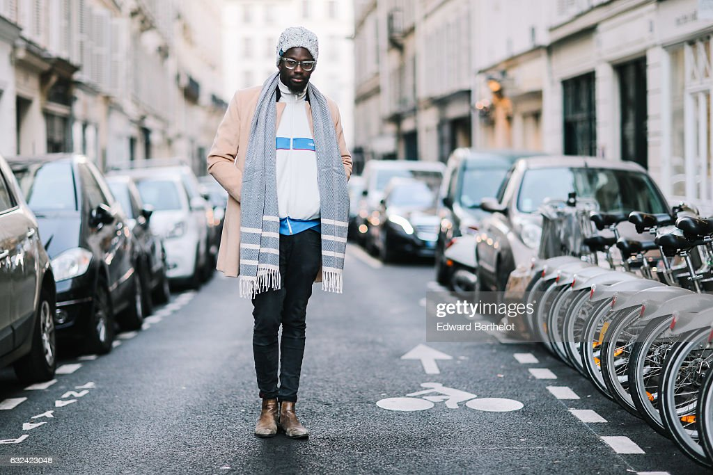 Sidya Sarr is wearing a Cortese watch, San Marina brown leather boots, an Zara striped top, a Zara gray scarf, a Superdry gray beanie hat, a camel long coat, and black pants, outside the Paul Smith show, during Paris Fashion Week Menswear Fall/Winter 2017/2018, on January 22, 2017 in Paris, France.