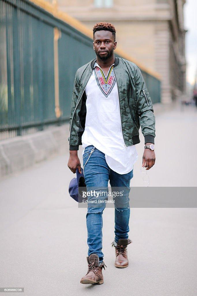 Sidya Sarr is wearing a green Asos jacket, a Versace watch, Asos blue denim slim jeans, a Dashiki white shirt, an Asos wallet chain, Zara shoes, an Atlanta baseball hat New Era, Stark Eyes sunglasses, on September 16, 2016 in Paris, France.