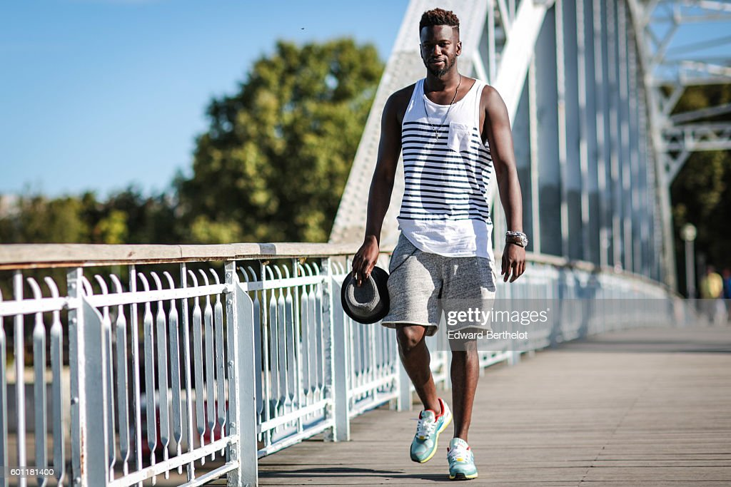 Sidya Sarr (lifestyle and fashion blogger), is wearing Adidas Torsion ZX 9000 shoes, a gray H&M short, an Asos wallet chain, a sleeveless t-shirt from Zara, a gray hat from Zara, Ray Ban sunglasses, and a Blomberg watch, on the bridge 'Passerelle Debilly', over the Seine river, on September 9, 2016 in Paris, France.