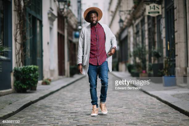 Sidya Sarr wears a hat a red checked shirt a white jacket blue denim jeans pants and brown shoes on February 19 2017 in Paris France
