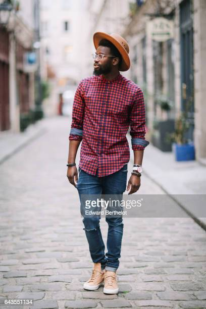 Sidya Sarr wears a hat, a red checked shirt, a white jacket, blue denim jeans pants, and brown shoes, on February 19, 2017 in Paris, France.