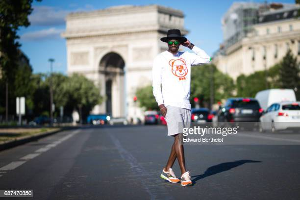 Sidya Sarr wears a hat from Asos a Dirty Nerdy white sweater with prints a short from Zara New Balance sneakers shoes and Hawkers glasses in front of...