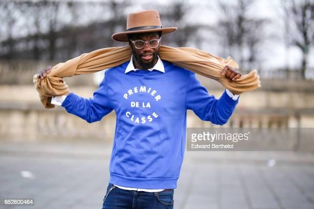 "Sidya Sarr wears a Zara beige scarf, an Asos beige hat, a Rad blue pull over with the inscription ""Premier de la Classe"", Asos blue denim jeans..."