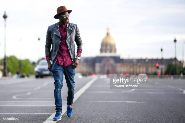 Sidya Sarr wears a Zara red tartan shirt an Asos leather perfecto black jacket Nike Cortez blue sneakers shoes a Zara hat Asos blue denim ripped...
