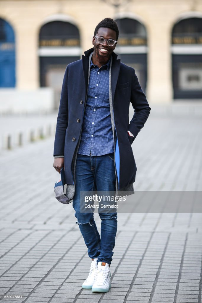 Sidya Sarr wears an Ice watch, Asos jewelry, an Asos shirt, a Zara jacket, a Bgarbo coat, a Nixon cap hat, Rayban glasses, Kevin Durant Nike shoes from Shinzo Paris, and Asos pants, on April 23, 2017 in Paris, France.