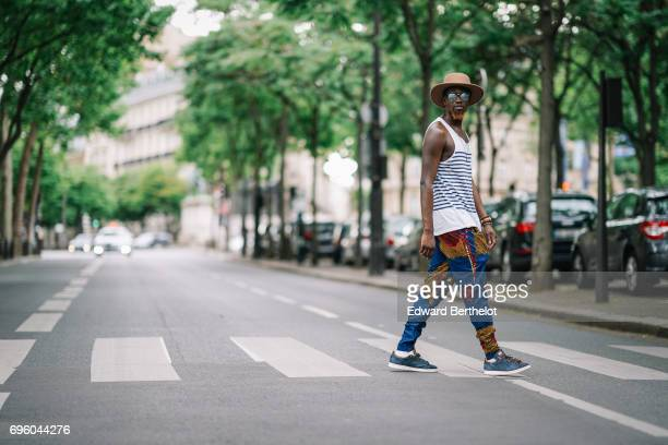 Sidya Sarr wears Stan Smith sneakers shoes a Zara striped sleeveless top a Zara tshirt blue pants with colored prints Rayban sunglasses an Asos hat...