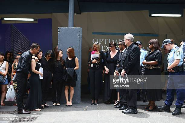 Siege victims comfort each other at a wreath laying ceremony after the funeral for Tori Johnson at Martin Place on December 23 2014 in Sydney...