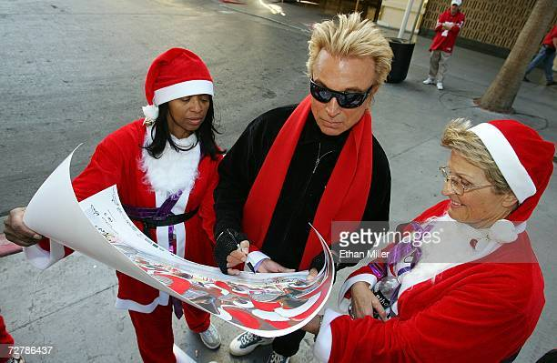 Siegfried Fischbacher of the illusionist duo Siegfried Roy signs an autograph for Wanda Wharton and Betty Allen after completing the onemile walk...