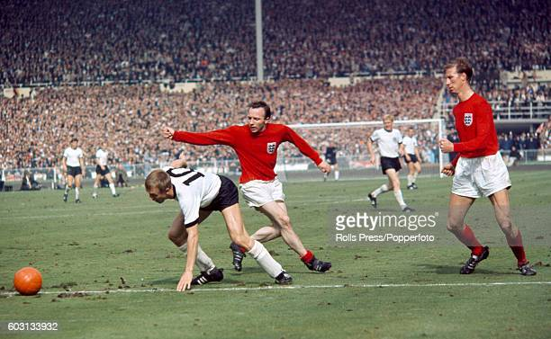 Siegfried Held of West Germany evades Nobby Stiles and Jack Charlton of England during the World Cup Final against West Germany at Wembley Stadium in...