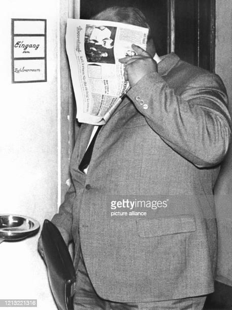 Siegfried Schramm der Ferbach 1962 in seiner Zeugenaussage schwer belastete verbirgt sein Gesicht hinter einer Zeitung aufgenommen während der...