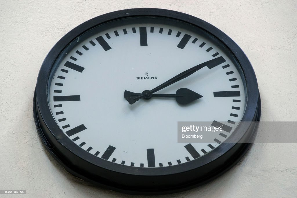 A Siemens AG branded clock sits on a wall in the training center inside the company's switchgear electronic power unit factory in Berlin, Germany, on Thursday, Sept. 13, 2018. Nearly one year afterSiemens unveiled a plan for massive jobs cuts at its struggling power and gas division, Chief Executive OfficerJoeKaesersaid talks with unions are nearing completion, clearing the way for a revamp of the business just as an industry slump deepens. Photographer: Krisztian Bocsi/Bloomberg via Getty Images