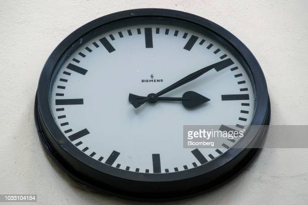 A Siemens AG branded clock sits on a wall in the training center inside the company's switchgear electronic power unit factory in Berlin Germany on...