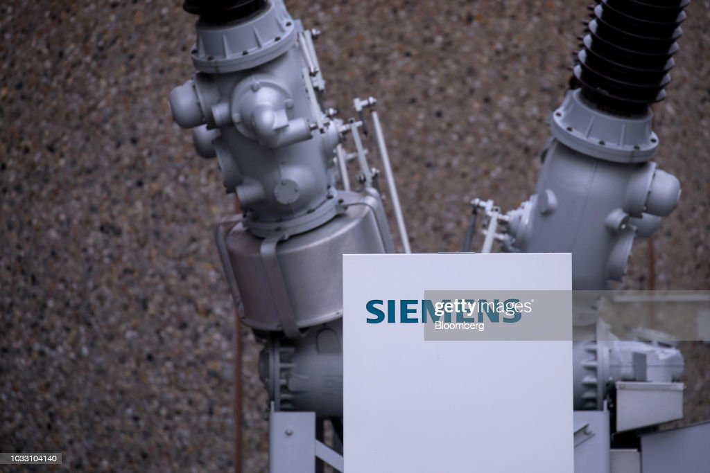 A Siemens company logo sits on a sign in front of a dead tank circuit breaker outside the Siemens AG switchgear electronic power unit factory in Berlin, Germany, on Thursday, Sept. 13, 2018. Nearly one year afterSiemens unveiled a plan for massive jobs cuts at its struggling power and gas division, Chief Executive OfficerJoeKaesersaid talks with unions are nearing completion, clearing the way for a revamp of the business just as an industry slump deepens. Photographer: Krisztian Bocsi/Bloomberg via Getty Images