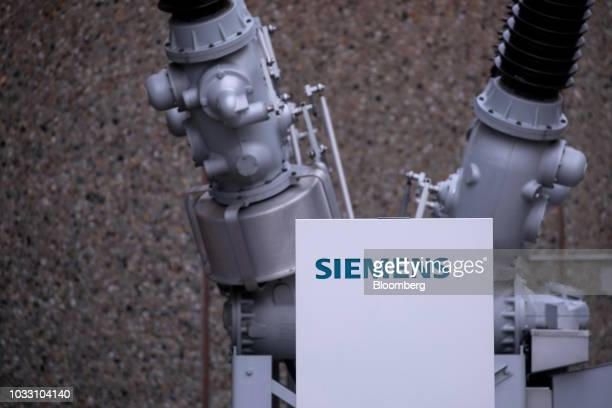 A Siemens company logo sits on a sign in front of a dead tank circuit breaker outside the Siemens AG switchgear electronic power unit factory in...