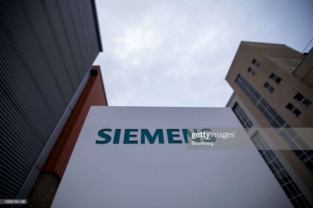 A Siemens company logo sits on a sign outside the Siemens AG switchgear electronic power unit factory in Berlin, Germany, on Thursday, Sept. 13, 2018. Nearly one year afterSiemens unveiled a plan for massive jobs cuts at its struggling power and gas division, Chief Executive OfficerJoeKaesersaid talks with unions are nearing completion, clearing the way for a revamp of the business just as an industry slump deepens. Photographer: Krisztian Bocsi/Bloomberg via Getty Images