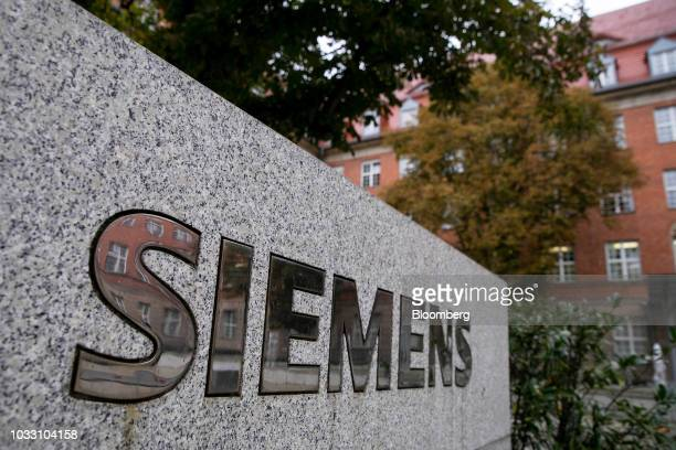 A Siemens company logo sits on a sign outside the Siemens AG switchgear electronic power unit factory in Berlin Germany on Thursday Sept 13 2018...