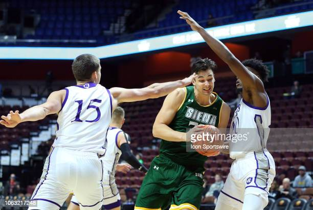 Siena Saints forward Evan Fisher defended by Holy Cross Crusaders forward Matt Faw and Holy Cross Crusaders forward Jehyve Floyd during a college...
