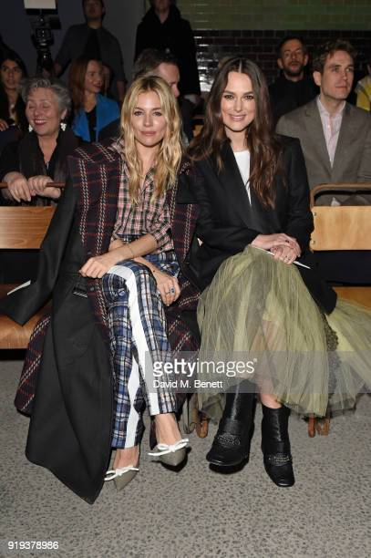 Sienna Miller and Keira Knightley wearing Burberry at the Burberry February 2018 show during London Fashion Week at Dimco Buildings on February 17...