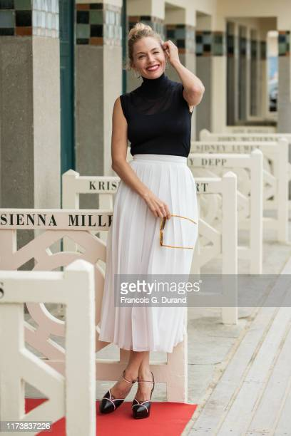 Sienna Miller poses for the photographers after she unveiled her cabin sign as a tribute for her career along the Promenade des Planches during the...