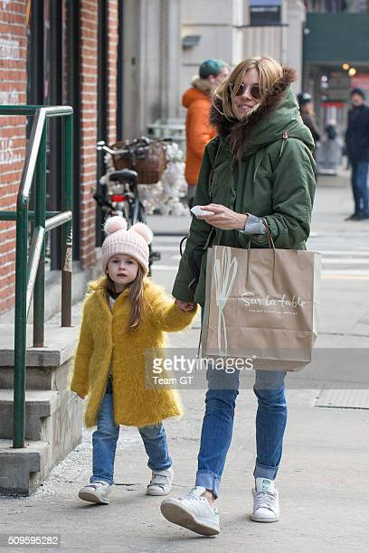 Sienna Miller stopping to get her daughter a cupcake while taking a walk through Soho