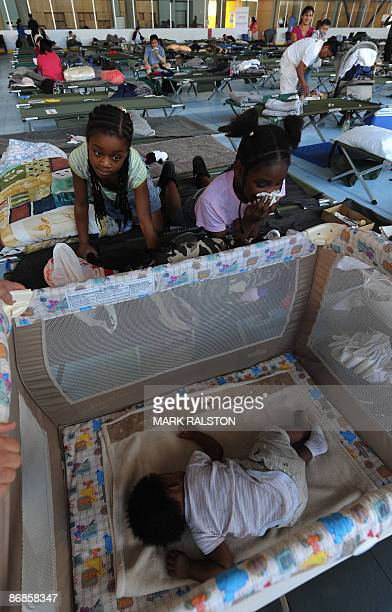 Sierra and sister Chelsie Ross watch their 7monthold brother Mekhl in his crib at the UCBS campus evacuation center after they were evacuated from...