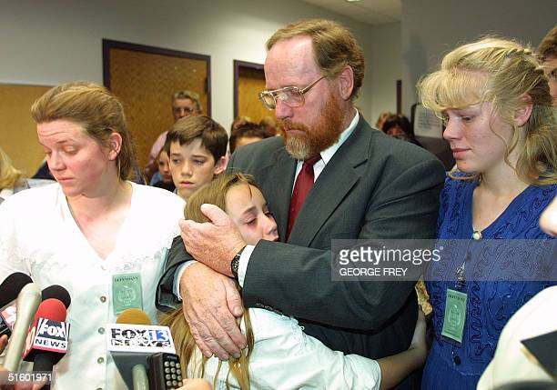 Sierra Green hugs her father Tom Green, flanked by two of his wives, Linda and Hannah , as he talks to reporters in Provo, Utah, late 18 May 2001....