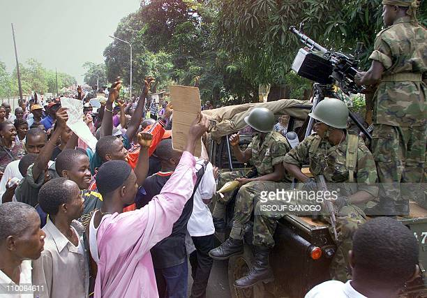 A Sierra Leonan soldier mans a heavy submachine gun atop a van outside Sierra Leone rebel leader Foday Sankoh 's residence as hundreds of protesters...