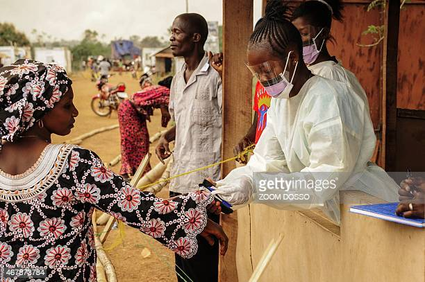 Sierra Leone health officials check passengers transiting at the border crossing with Liberia in Jendema on March 28 2015 The authorities in Sierra...