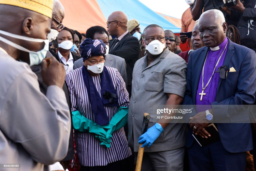 Sierra Leone President Ernest Bai Koroma (2nd L, with glasses) and Liberian President Helen Johnson Sirleaf (C) lay flowers on coffins of mudslide victims on August 17, 2017 at Waterloo cemetery near Freetown, Sierra Leone. Sierra Leone buried at least 300 victims of devastating floods on Thursday, as fears grew of more mudslides and accusations of government 'inaction' over deforestation and poor urban planning mounted. With the aim of clearing the overflowing central morgue, burials began around 1800 GMT in Waterloo, a nearby town where many victims of the Ebola crisis that hit the nation in 2014 were also laid to rest, according to a morgue official and an AFP journalist at the scene. PHOTO / SEYLLOU