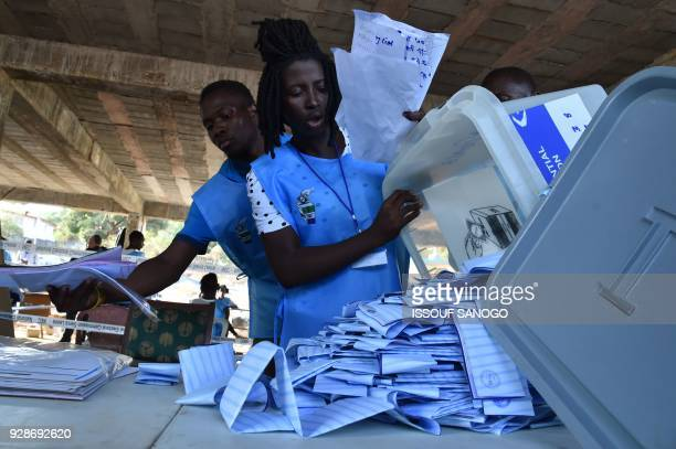 Sierra Leonean election workers empty a box containing ballot papers as counting takes place at a polling station in Freetown on March 7 following...