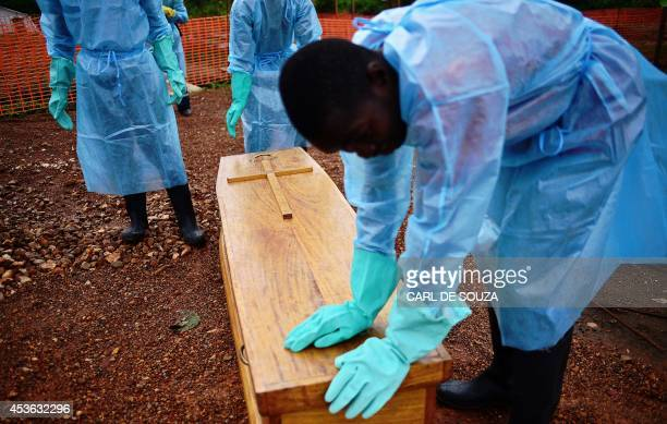 Sierra Leonese government burial team members wearing protective clothing stand next to the coffin of Dr Modupeh Cole Sierra Leone's second senior...