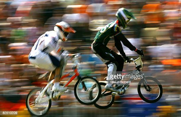 Sifiso Nhlapo of South Africa and Raymon van der Biezen of the Netherlands compete in the Men's BMX semifinal run held at the Laoshan Bicycle Moto...