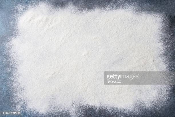 Sifted wheat flour over dark blue texture surface Food background