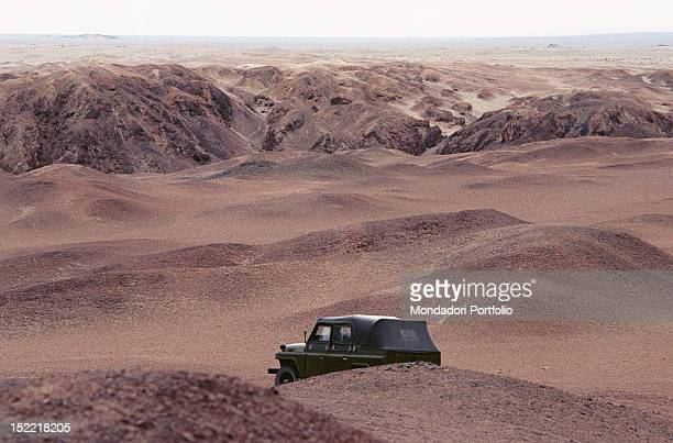 A sight of the big stony ridges of the upland where Gobi desert spreads between China and Mongolia a green jeep runs through the desert with its dome...