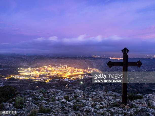 Sight raised from the top of a mountain with twilight light of a people with the lights ignited at the back of a valley and a sky of changeable colors. Town of Bocairent, Valencian Community, Spain, Spain