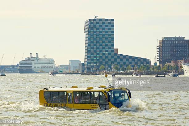 Sightseeing amphibian bus driving through Rotterdam harbor