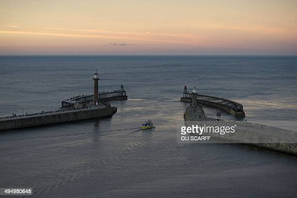 A sightseeing boat leaves Whitby harbour at sunset in Whitby northern England on October 30 2015 AFP PHOTO / OLI SCARFF