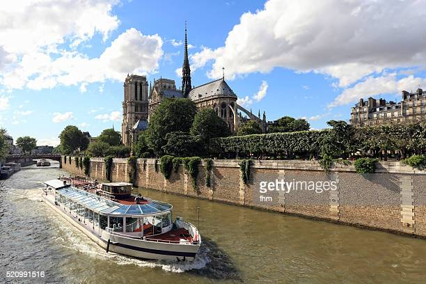 A sightseeing boat on Seine River in Paris is passing Notre Dame