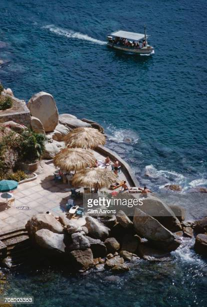 A sightseeing boat passes a resort hotel on the coast at Acapulco Mexico 1961