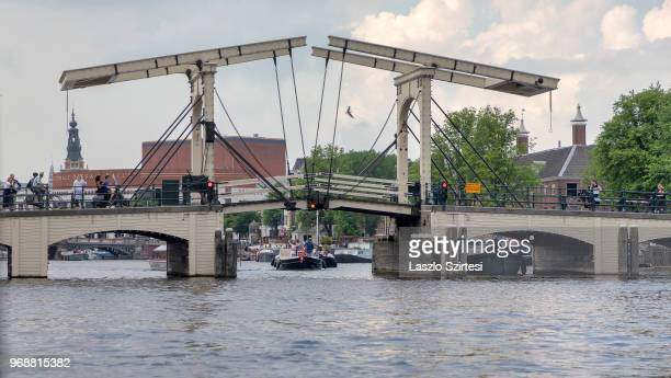 Sightseeing boats pass under the Magere Brug Bridge on May 30 2018 in Amsterdam Netherlands This moveable bridge over the Amstel river is the...