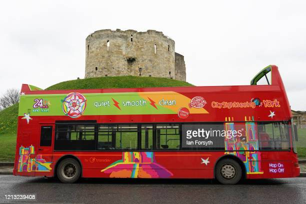 A sightseeing bus stands empty next to Clifford's Tower as the UK adjusts to life under the Coronavirus pandemic on March 18 2020 in York England...