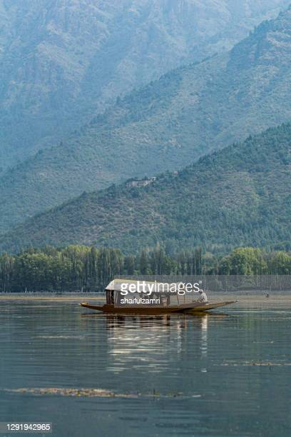 sightseeing over dal lake using a shikara - a type of wooden boat. - shaifulzamri stock pictures, royalty-free photos & images