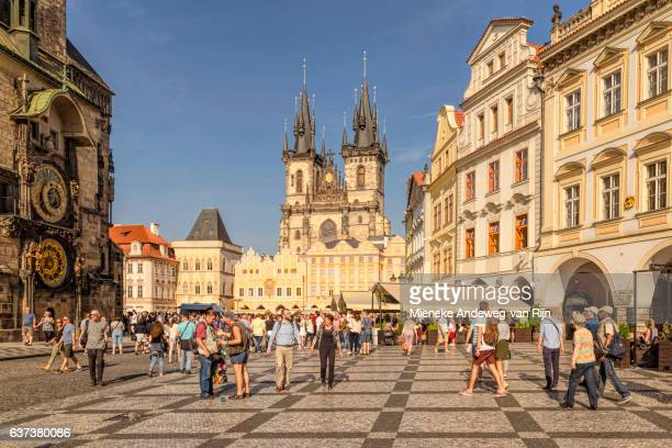 Sightseeing tourists in The Old Town Square with view on the church of Our Lady Before Tyn, Prague, Czech Republic.