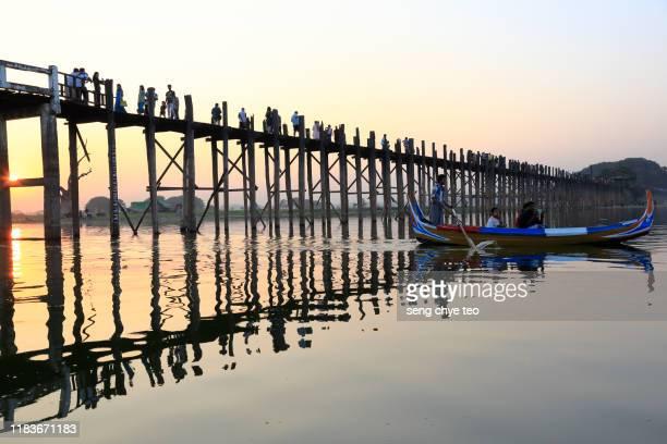 sightseeing wooden boat across u bein bridge, mandalay, myanmar - teak wood material stock pictures, royalty-free photos & images