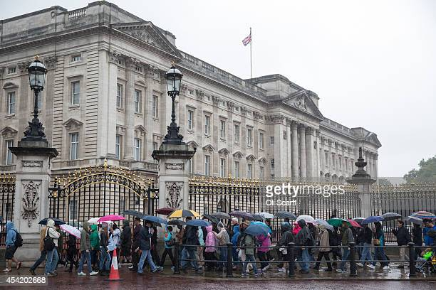 Sightseers admire the area surrounding Buckingham Palace in inclement weather on August 26 2014 in London England Many areas of England especially...