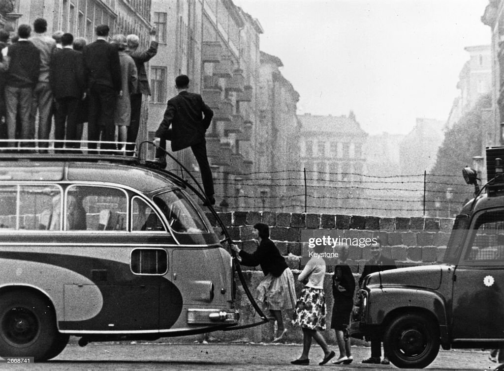 Sightseers climb onto a bus to look at the newly-built Berlin Wall.