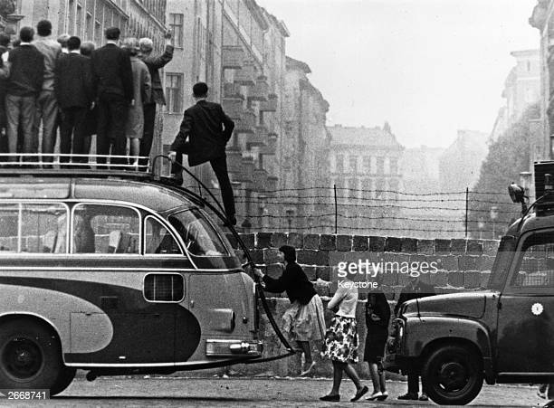 Sightseers climb onto a bus to look at the newlybuilt Berlin Wall