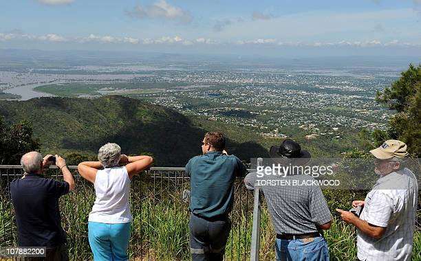 Sightseers gather on the summit of Mt Archer to watch flood waters inundate much of Rockhampton on January 5 2011 after the swollen Fitzroy River...