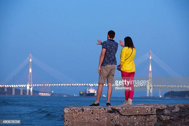 Sightseers look out across the Eastern Bosphorus strait from the shoreline towards the Russian bridge in Vladivostok Russia on Saturday Sept 26 2015...